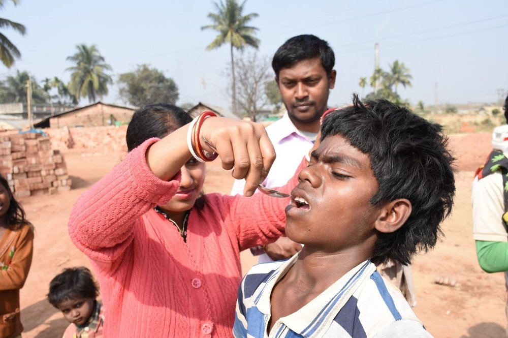 Photo 3: A multi-purpose health worker gives Rohit deworming tablets at the brick kiln on NDD in Jirania, West Tripura