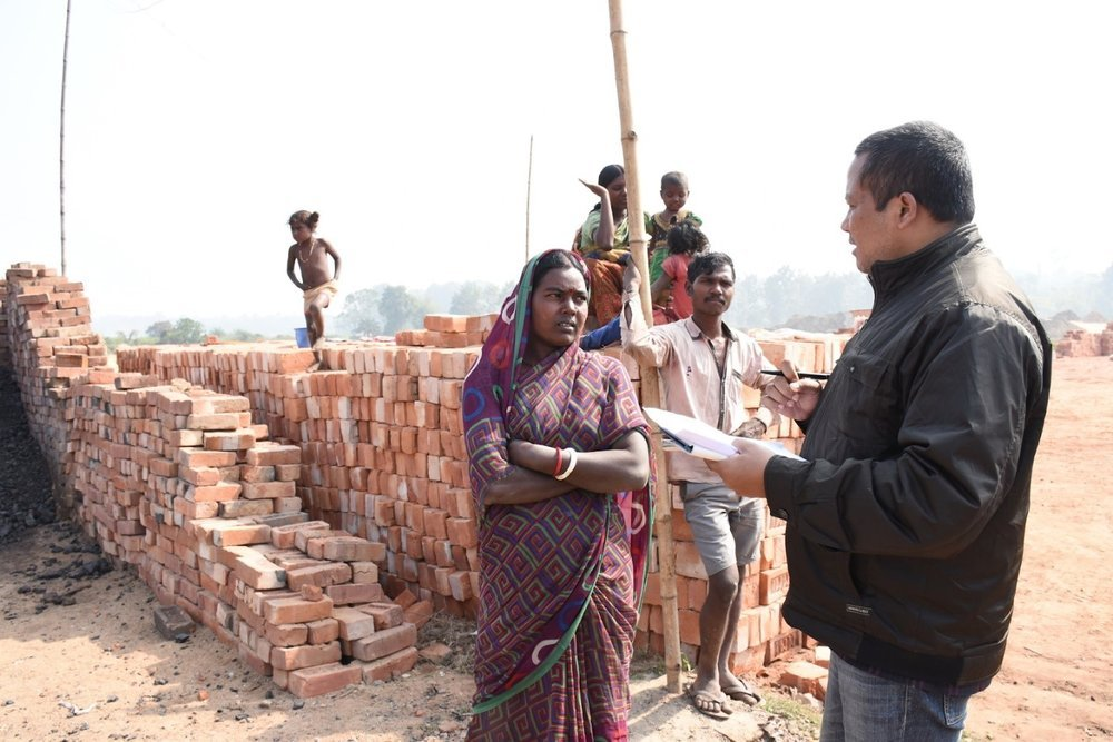 Photo 2: Evidence Action India team member, Sanjoy Yumnam talks to Guddi at the brick kiln in Jirania, West Tripura